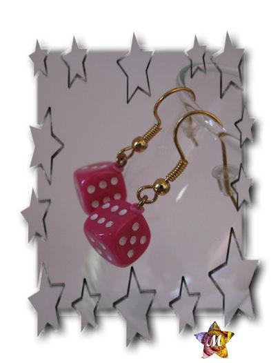 boucles d oreilles dorées avec un petit dé rose
