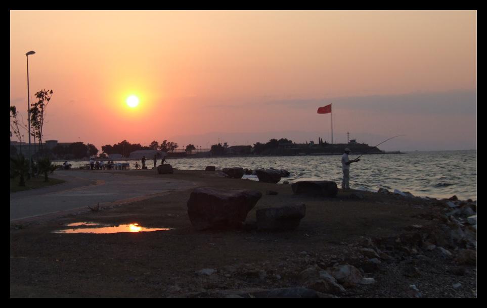 pêcheur à la ligne au soleil couchant