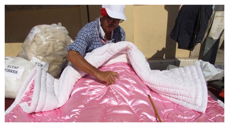 L' artisan coud un couvre-pieds